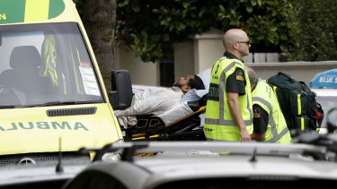 Ambulance staff take a man from outside a mosque in central Christchurch following a mass shooting.