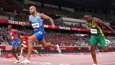 Italian Lamont Marcell Jacobs crosses the line first in the men's 100m final at Olympic Stadium.