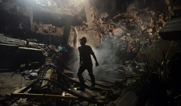 A rescue worker leaves the site where a garment factory building collapsed near Dhaka, Bangladesh.