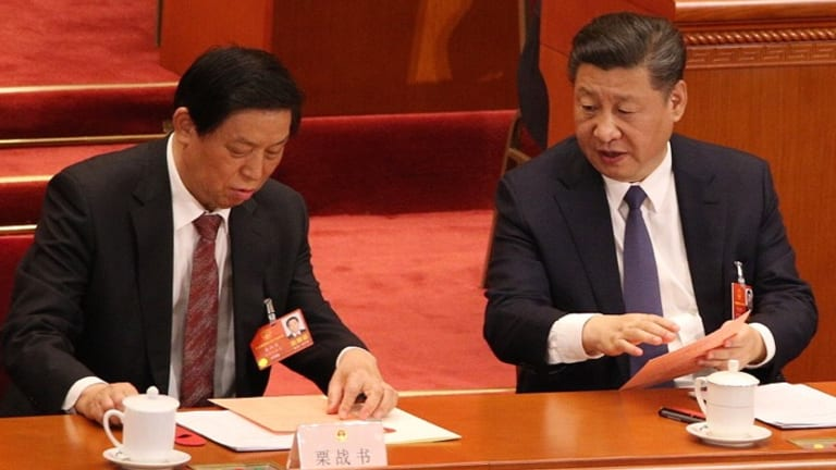 Chinese president Xi Jinping, right, talks to his colleague Li Zhanshu, a member of the standing committee of politburo before deputies to the First Session of 13th National People's Congress voted for Constitution amendment.