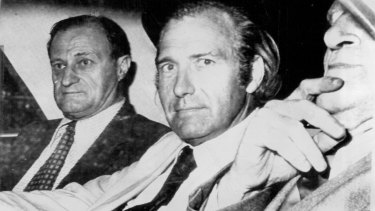 Stonehouse (centre) being driven by police from his apartment in the Centre City Club, Melbourne.