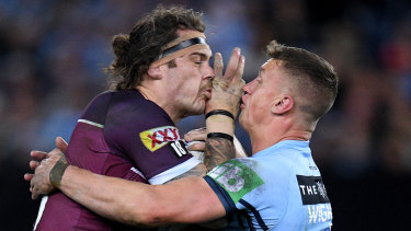 Lowe being tackled by Jack Wighton of the Blues during Game 3 of the State of Origin series on Wednesday.