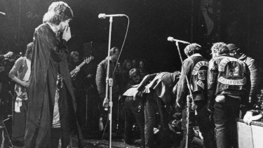 Mick Jagger looks on as the Hells Angels dragged an unidentified person  onstage at  the Altamont  rock festival at Livermore, California, Dec 6, 1969.
