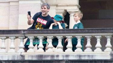 Queensland Greens MP Michael Berkman on the balcony in Parliament while wearing an anti-Adani T-shirt.