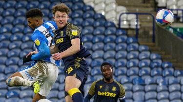 Harry Souttar wins an aerial battle against Huddersfield Town's Fraizer Campbell.