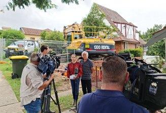 Toowong residents John Scott and Freya Robertson express their concerns as bulldozers remove Linden Lea at Toowong.