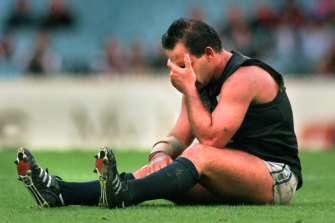 Greg Williams sits stunned on the ground after being hit in a match against Essendon.