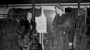 Two women take advantage of the sale on fur coats at David Jones during the heatwave of 1938-1939, Sydney, 17 February 1939.