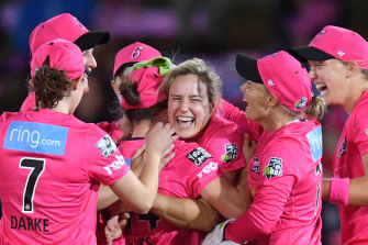 Ellyse Perry, centre, celebrates with her Sixers teammates after taking the wicket of Rachel Priest.