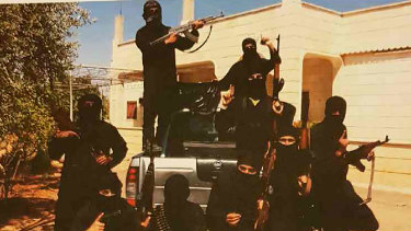Mehmet Biber poses with insurgents in Syria. He is pictured inside the tray of the vehicle wearing a white watch.