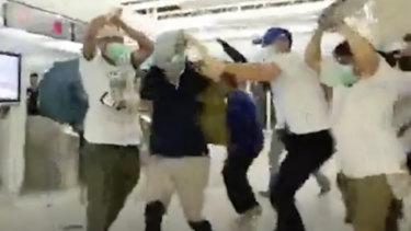 Masked men attack people at Yuen Long metro station.