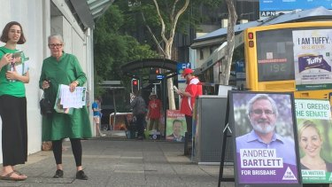 Volunteers armed with how-to-vote cards outside the Brisbane City early voting centre on Queen Street on Friday.