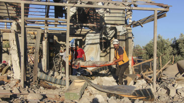 This photo released by the Syrian Civil Defence White Helmets in Daraa, shows civil defence workers carrying a victim from a house, after shelling by Syrian government forces, in the town of Nawa, Daraa, southern Syria.