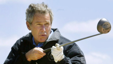 George W.  Bush points a golf club at a reporter while refusing to answer a question during his presidency.