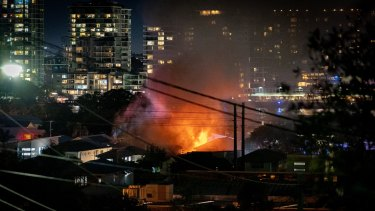 Flames visible on the Brisbane CBD skyline as the Bulimba home burns on Sunday.