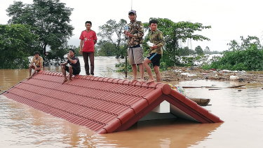 Lao villagers are stranded on a roof of a house due to floodwaters after the dam collapsed