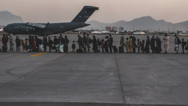 Evacuees wait to board a C-17 at Hamid Karzai International Airport in Kabul.