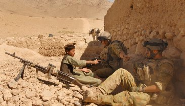 An Afghan boy sits with Australian Reconstruction Task Force soldiers during a meeting with local leaders in Oruzgan Province, Afghanistan.