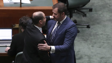 Josh Frydenberg and Ed Husic embrace on the floor of Parliament after condemning a divisive speech given by Fraser Anning.