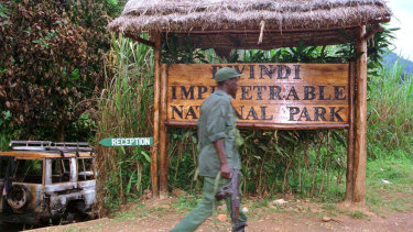 A Ugandan soldier walks past the entrance of the Bwindi Impenetrable National Park the week of the murders.