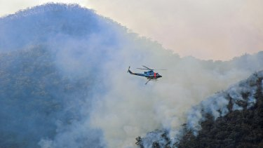 A helicopter waterbombing fires on NSW's south coast in mid-August.