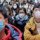 People wear face masks as they wait at Hankou Railway Station in Wuhan last week.