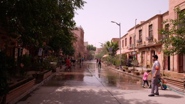 A shop keeper wearing a civilian security volunteer armband hoses down the street to beat the heat.