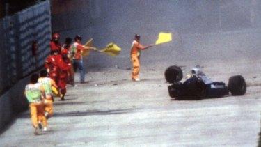 Race officials run towards Ayrton Senna's car after he crashed at Imola in 1994.