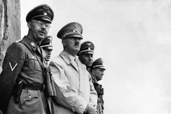Heinrich Himmler (left) stands with Adolf Hitler to observe a parade of Nazi Stormtroopers in 1940.