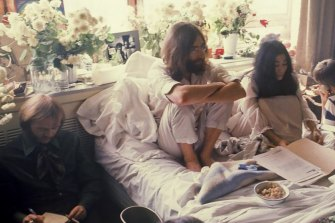 Ritchie Yorke, with notebook (on left) beside John Lennon and Yoko Ono at one of the  Bed In peace conferences.