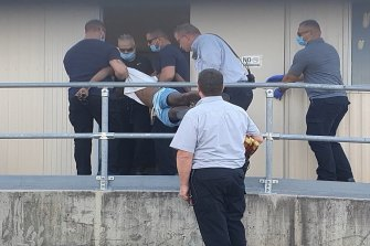 Officials carry one of the men into a room at the Brisbane Immigration Transit Accommodation site.