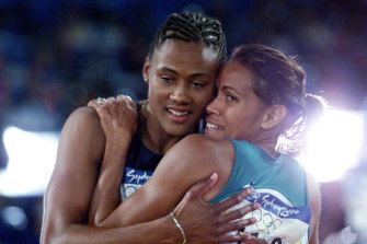 Marion Jones is congratulated by Cathy Freeman after winning the 200m final.