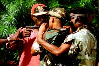 The personal bodyguard of the sacked head of PNG's armed forces threatens another soldier during unrest in 1997.