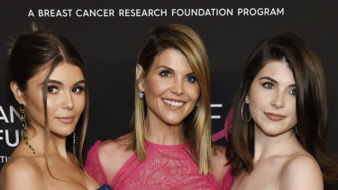 Lori Loughlin (centre) pictured with daughters Olivia (left) and Isabella, was charged with paying $US500,000 to ensure her daughters' entry to elite universities.