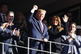 President Donald Trump and first lady Melania Trump wave to the crowd at the game between the LSU Tigers and the Alabama Crimson Tide in Tuscaloosa, Alabama.