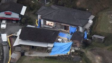 Blue plastic sheets cover the site where six bodies believed to be members of a family were found at a farmhouse in Takachiho.