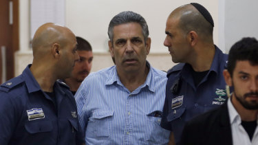 Former Israeli cabinet minister Gonen Segev, centre, escorted by prison guards as he arrives at court in Jerusalem in July 2018.