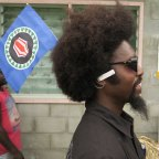 A man plants a Bougainville flag in his hair as he queues up to vote on the opening day of the territory's independence referendum.