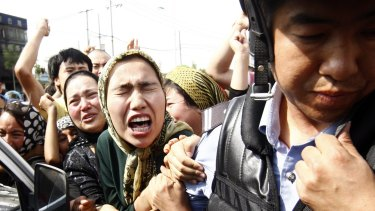 An angry crowd belonging to the Chinese Uyghur Muslim minority try to grab hold of a police officer during protests in Urumqi, China, in 2009.