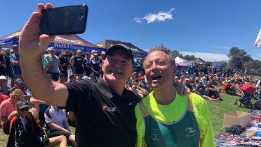 Australian marathon legend Rob de Castella takes a selfie with 81-year-old triathlete Lachlan Lewis.
