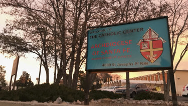 The sun sets on a sign in front of the Archdiocese of Santa Fe offices in Albuquerque. The archdiocese is in bankruptcy proceedings as a result of the abuse scandal involving 70 clergy members.