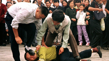 Police detain a Falun Gong protester in Tiananmen Square as a crowd watches in Beijing.