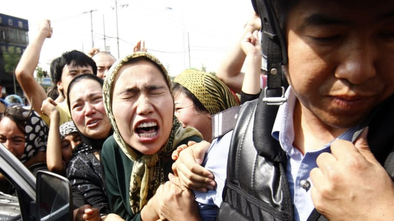 An angry crowd belonging to the Chinese Uyghur Muslim minority try to grab hold of a police officer during new protests in Urumqi, China, in 2009.