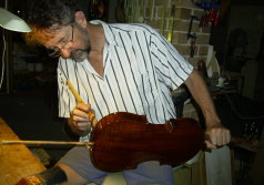 Graham Caldersmith varnishes a violin.