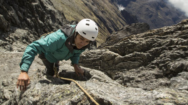 Scientist Cherry Andrea Rojas scales rocks during an expedition to the Humbolt glacier.