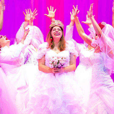 Natalie Abbott (centre) stars as Muriel Heslop in Muriel's Wedding The Musical.