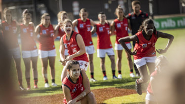 Essendon VFLW players, Indigenous and non-indigenous, participate in a Unity dance prior to the VFLW match between Richmond and Essendon at Punt Road in 2018.