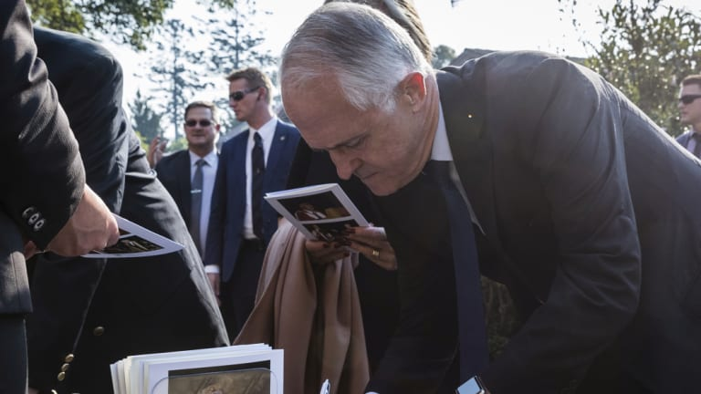 Malcolm Turnbull and his wife, Lucy, sign the condolence book outside the memorial service for Sir John Carrick.