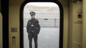 A police officer is seen through a train window as he stands on a platform at a railway station in Turpan, Xinjiang autonomous region, China, on Tuesday, Nov. 6, 2018. Although it represents just 1.5 percent of China's population and 1.3 percent of its economy, Xinjiang sits at the geographic heart of Xi's signature Belt and Road Initiative. Source: Bloomberg