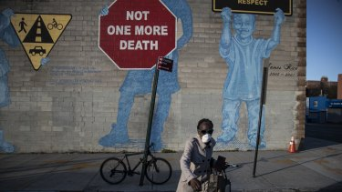 "A woman wearing a mask crosses the street in front of a mural about traffic accidents reading, ""NOT ONE MORE DEATH"" in the Brooklyn borough of New York."